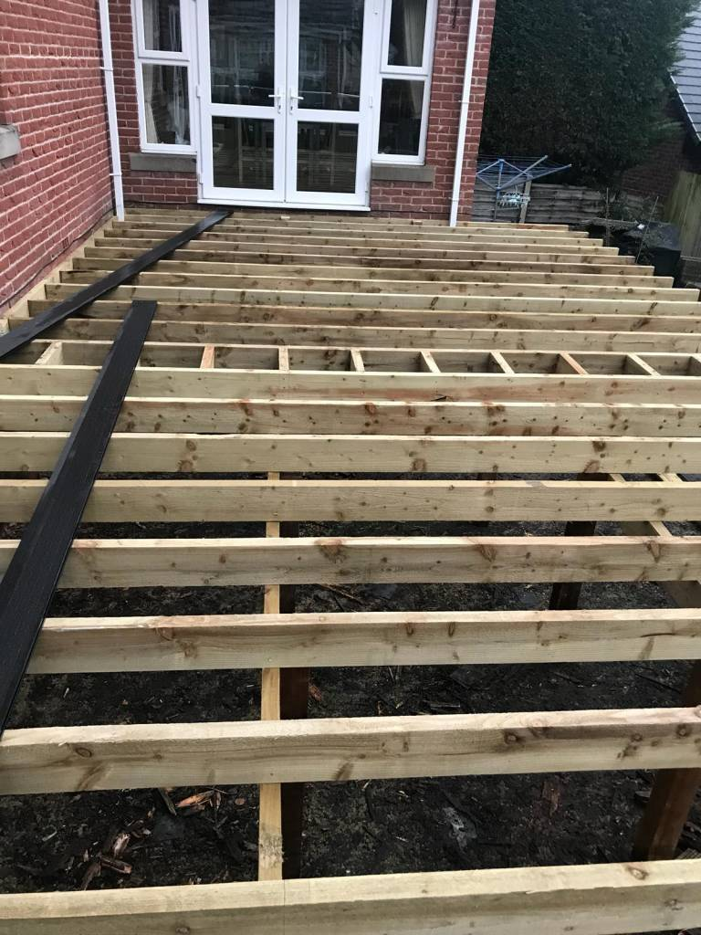 A decking area being laid by oakmere landscaping ltd in salford, greater manchester